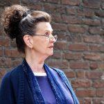 Frau mit Brille vor Backsteinwand