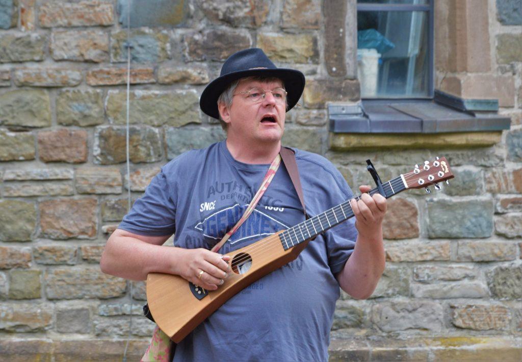 Mann singt mit Gitarre