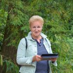 Frau mit ipad in front of a tree