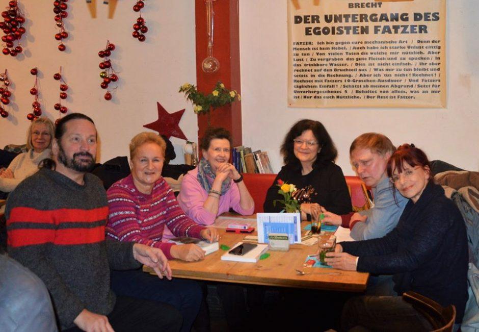 Gruppe Männer und Frauen sitzen am Tisch