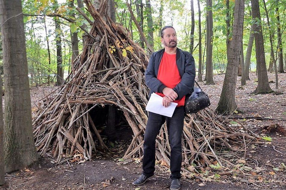 Mann mit Papier steht im Wald